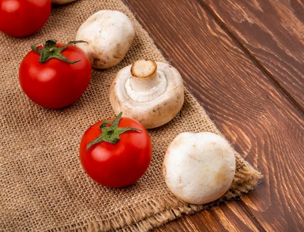 Seitenansicht des champignons der frischen pilze und der frischen tomaten auf sackleinen auf hölzernem hintergrund Kostenlose Fotos