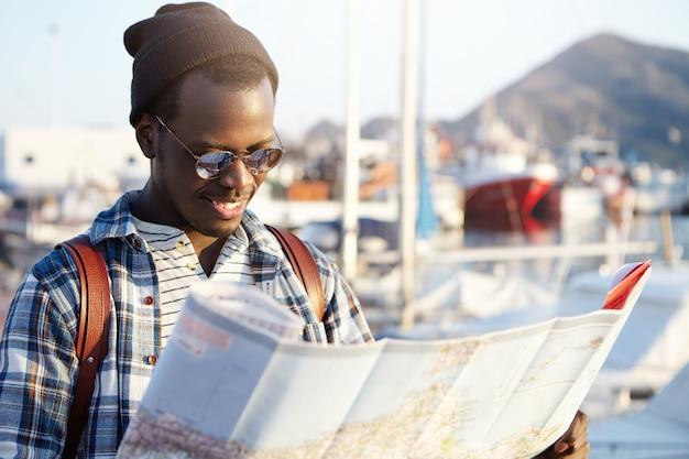 Seitenansicht des dunkelhäutigen touristen mit rucksack im trendigen hut und in der sonnenbrille, die richtungen unter verwendung seiner papierstraßenkarte untersuchen. yachtpark oder club im malerischen ferienort Kostenlose Fotos