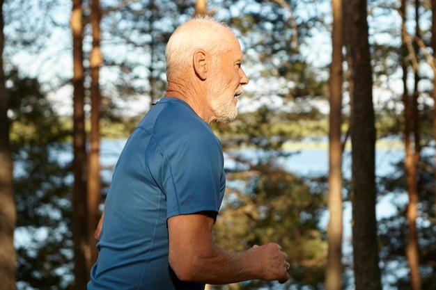 Seitenansicht des energetisch aktiven älteren mannes mit grauem haar, bart und muskulösem körper, der schnell im wald entlang des flussufers läuft und einen gesunden lebensstil und frische morgenluft genießt. action-schuss Kostenlose Fotos
