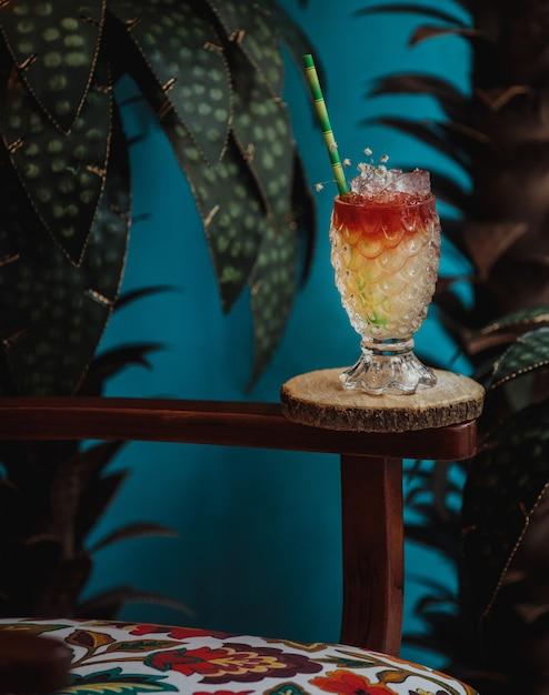 Seitenansicht des exotischen cocktails im geprägten glas in einem hölzernen ständer auf grüner wand Kostenlose Fotos
