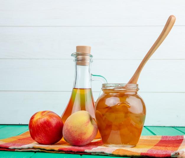 Seitenansicht des frischen fruchtapfels mit pfirsich und einer flasche olivenöl und pfirsichmarmelade in einem glas mit einem holzlöffel auf grünem holzhintergrund Kostenlose Fotos