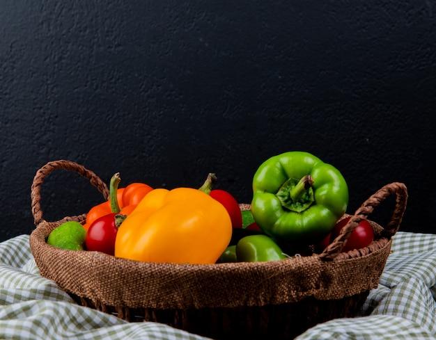 Seitenansicht des frischen gemüses bunte paprika-tomaten und gurken in einem weidenkorb auf kariertem stoff auf schwarz Kostenlose Fotos