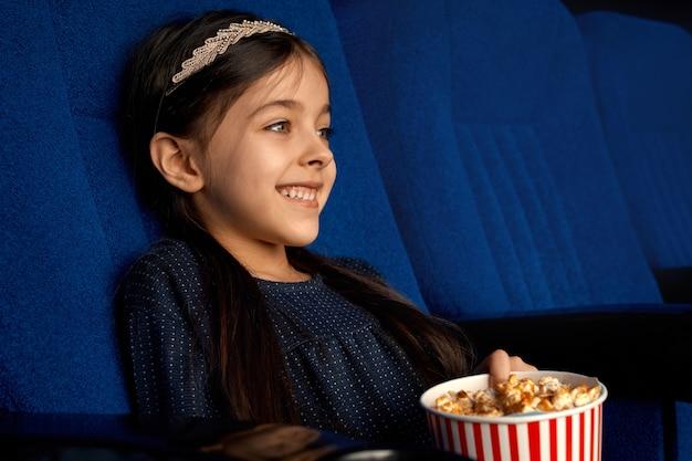 Seitenansicht des fröhlichen brünetten mädchens mit ponnytail, das über lustige komödie im kino lacht. glückliches weibliches kind, das popcorn isst und am wochenende entspannt Kostenlose Fotos