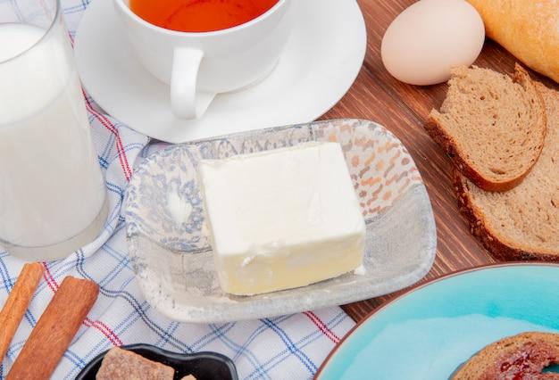 Seitenansicht des frühstückssets mit butterroggenbrotscheiben, die mit marmelade in tellermilch-zimt-tee auf kariertem stoff und holztisch verschmiert sind Kostenlose Fotos