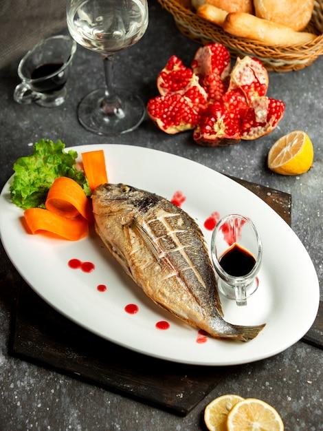 Seitenansicht des gebackenen wolfsbarsches serviert mit lemonnd narsharab sauce auf weißer platte auf schwarz Kostenlose Fotos