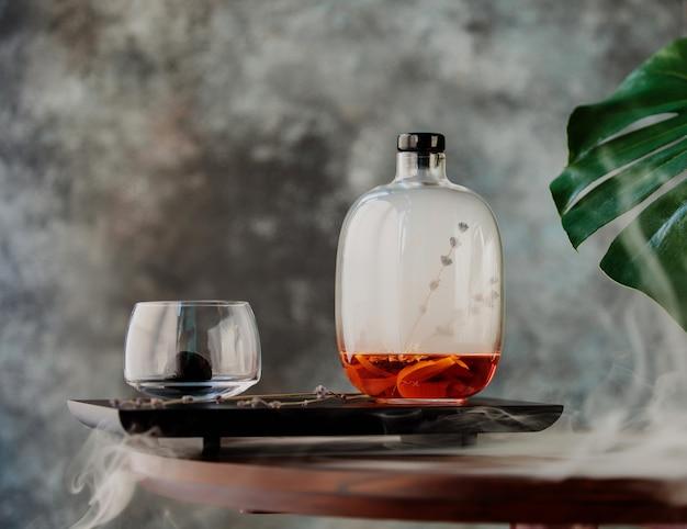 Seitenansicht des glühweins in einer dekorativen glasflasche auf einem holzbrett Kostenlose Fotos