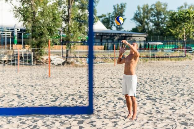 Seitenansicht des hemdlosen männlichen volleyballspielers, der mit ball am strand übt Kostenlose Fotos