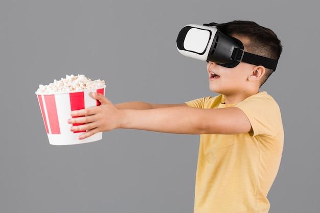 Seitenansicht des jungen, der popcorn hält und virtual-reality-headset trägt Kostenlose Fotos