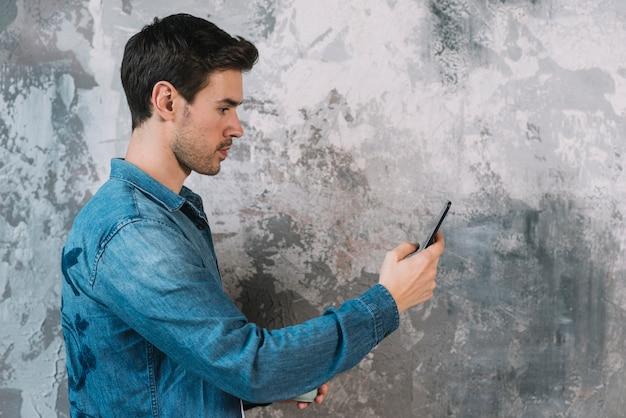 Seitenansicht des jungen mannes stehend vor schmutzwand unter verwendung des mobiltelefons Kostenlose Fotos