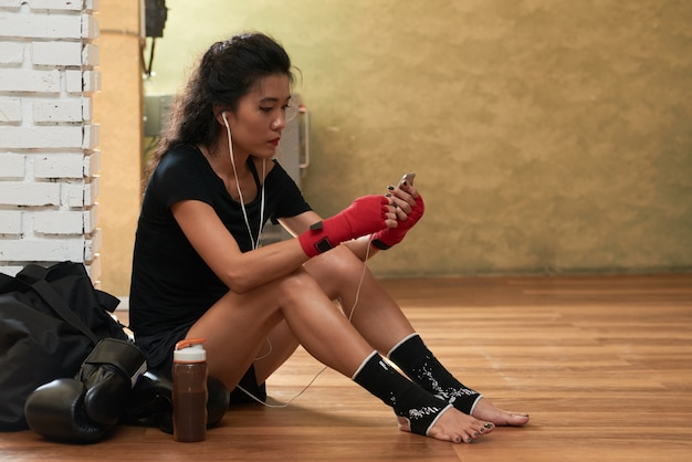 Seitenansicht des jungen weiblichen athleten, der musik nach dem training hört Kostenlose Fotos
