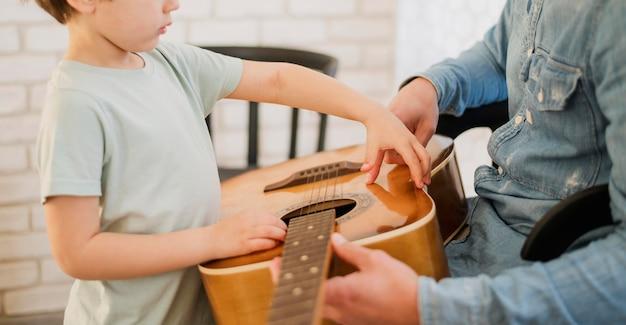Seitenansicht des kindes und des gitarrenlehrers Kostenlose Fotos