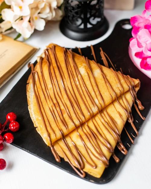 Seitenansicht des krepps mit schokoladenkakaosirup auf einem hölzernen schneidebrett Kostenlose Fotos