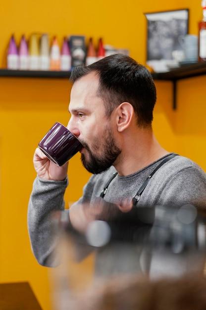Seitenansicht des männlichen barista, der kaffee trinkt Kostenlose Fotos