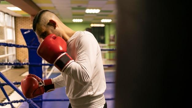 Seitenansicht des männlichen boxers, der mit boxsack im ring übt Kostenlose Fotos