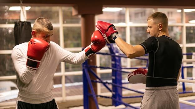 Seitenansicht des männlichen boxers, der mit trainer neben ring übt Kostenlose Fotos