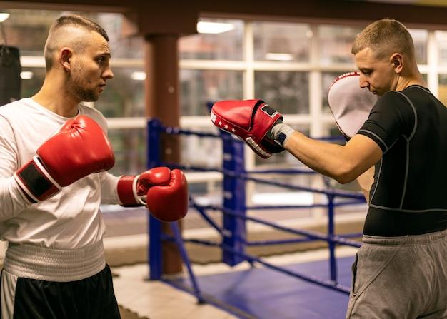 Seitenansicht des männlichen boxers, der mit trainer übt Kostenlose Fotos