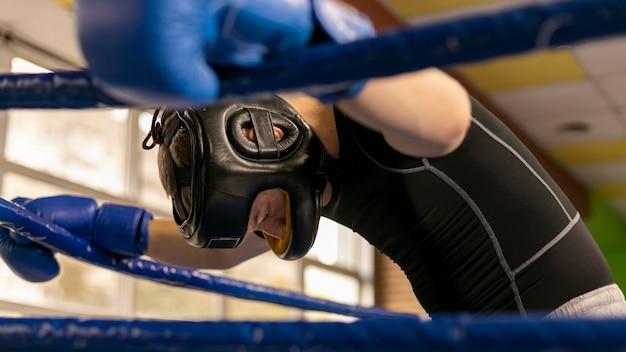 Seitenansicht des männlichen boxers mit handschuhen und helm im ring Premium Fotos