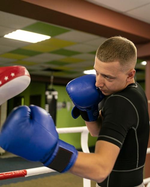 Seitenansicht des männlichen boxers mit trainer neben dem boxring Kostenlose Fotos