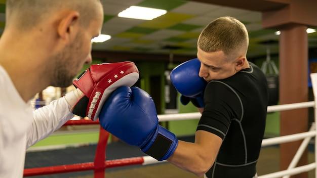 Seitenansicht des männlichen boxers mit trainer neben ring Kostenlose Fotos
