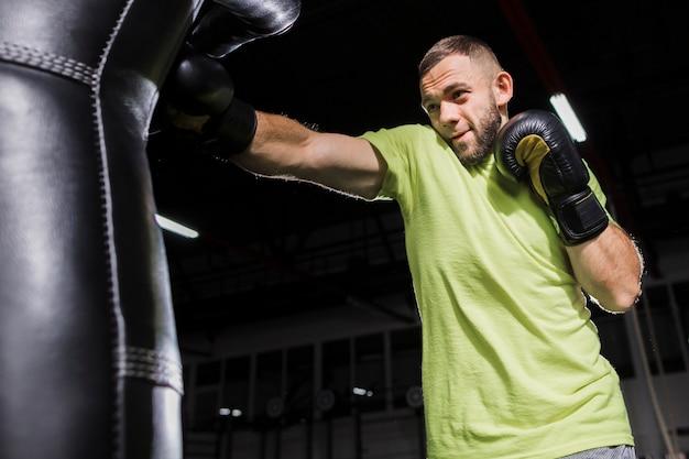 Seitenansicht des männlichen boxers übend mit sandsack Kostenlose Fotos