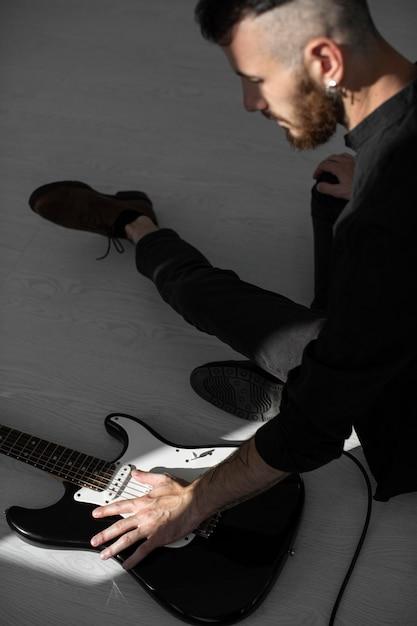 Seitenansicht des männlichen darstellers, der e-gitarre spielt Kostenlose Fotos