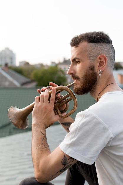 Seitenansicht des männlichen künstlers, der das kornett auf dach spielt Premium Fotos