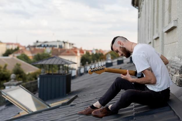 Seitenansicht des männlichen musikers auf dem dach, der e-gitarre spielt Kostenlose Fotos