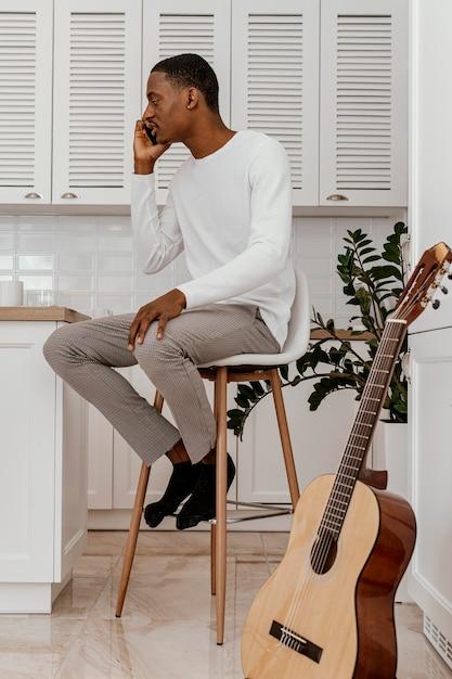 Seitenansicht des männlichen musikers, der am telefon neben der gitarre spricht Premium Fotos
