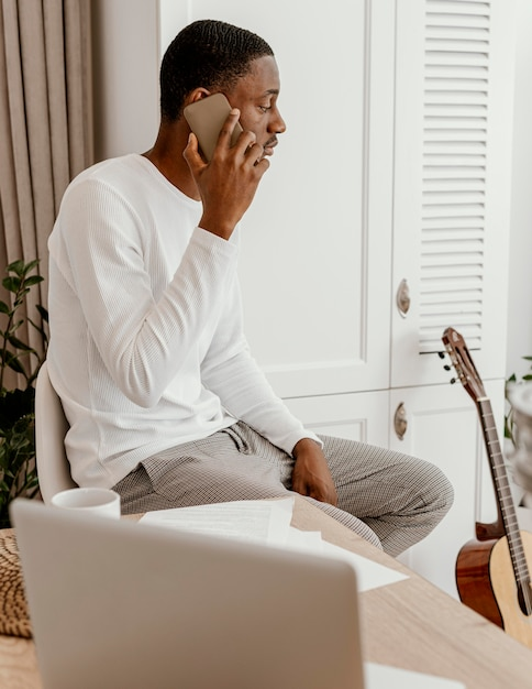 Seitenansicht des männlichen musikers, der auf dem smartphone neben der gitarre spricht Premium Fotos