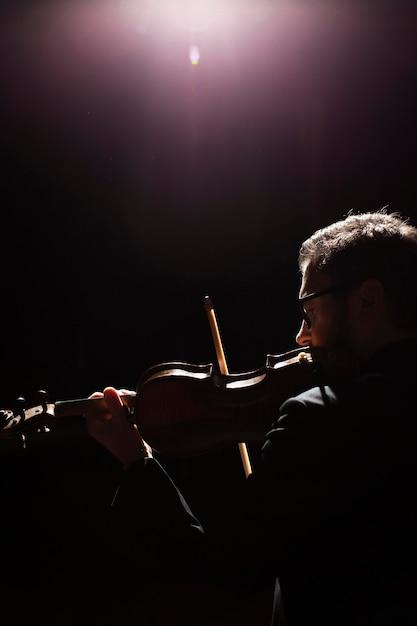 Seitenansicht des männlichen musikers, der die geige mit kopienraum spielt Kostenlose Fotos