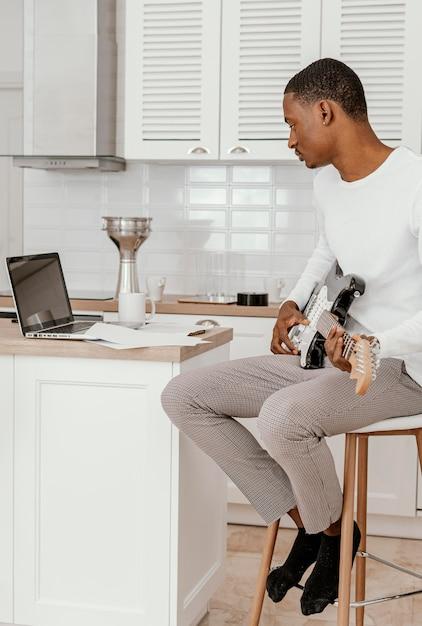 Seitenansicht des männlichen musikers, der elektrische gitarre spielt und laptop betrachtet Premium Fotos