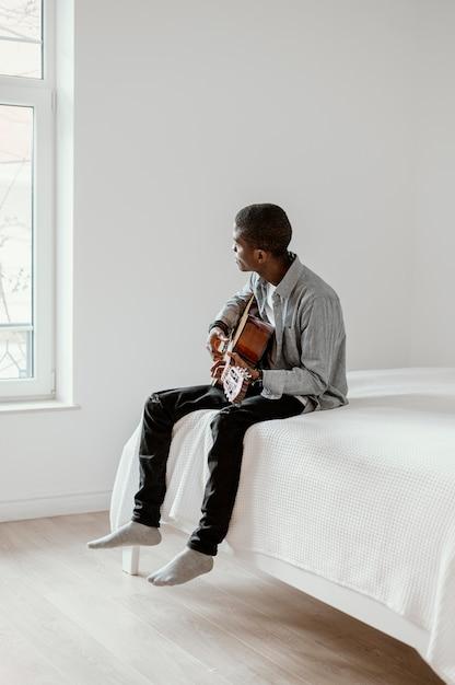 Seitenansicht des männlichen musikers mit gitarre Kostenlose Fotos