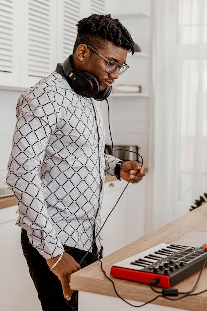 Seitenansicht des männlichen musikers mit kopfhörern und elektrischer tastatur Premium Fotos