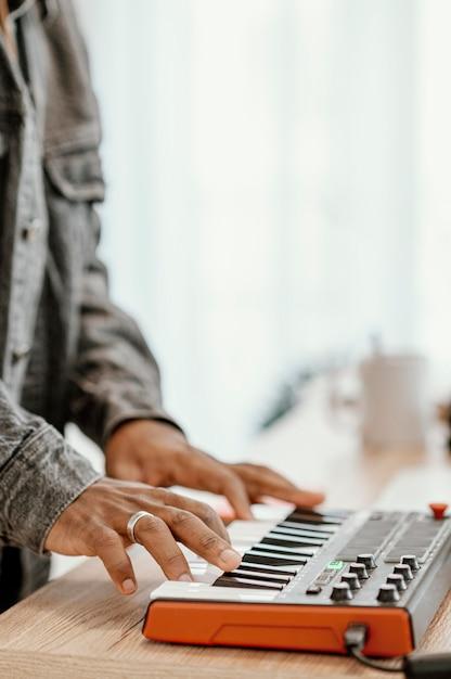 Seitenansicht des männlichen musikers zu hause, der elektrische tastatur spielt Kostenlose Fotos