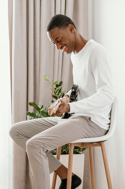 Seitenansicht des männlichen smiley-musikers, der zu hause e-gitarre spielt Premium Fotos