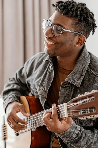 Seitenansicht des männlichen smiley-musikers, der zu hause gitarre spielt Kostenlose Fotos