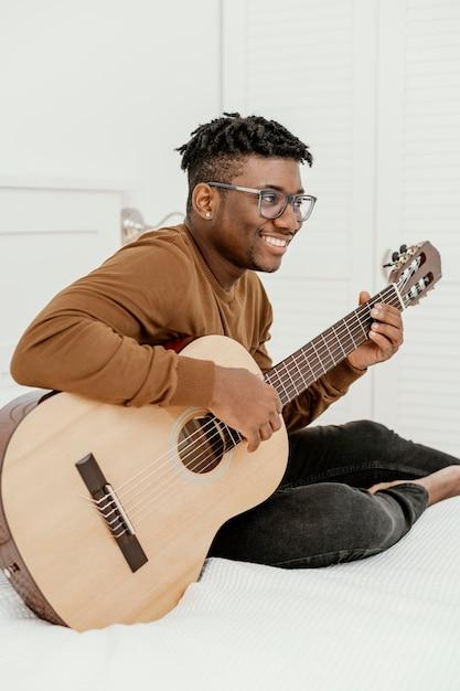 Seitenansicht des männlichen smiley-musikers zu hause, der gitarre auf bett spielt Kostenlose Fotos