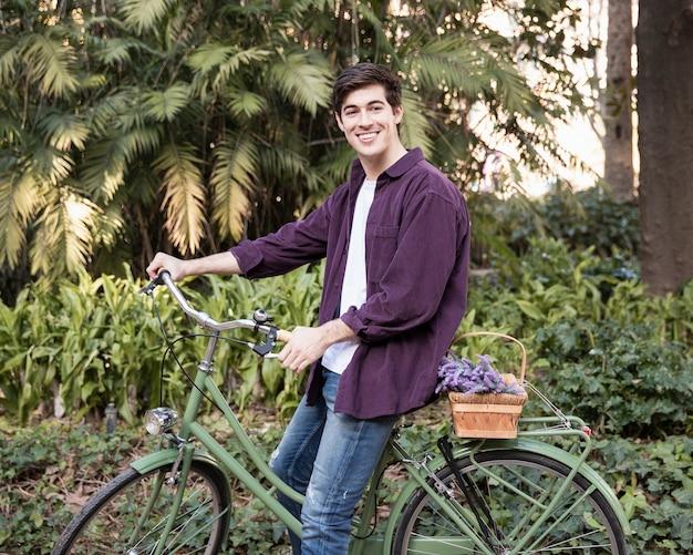 Seitenansicht des mannes auf dem fahrrad am park Kostenlose Fotos