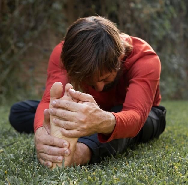 Seitenansicht des mannes, der auf dem gras draußen während des yoga streckt Premium Fotos