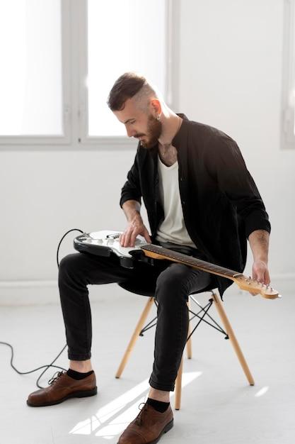 Seitenansicht des mannes, der e-gitarre spielt Kostenlose Fotos