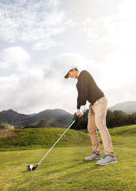 Seitenansicht des mannes, der golf auf dem feld mit verein und kopienraum spielt Kostenlose Fotos