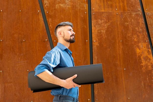 Seitenansicht des mannes gebäudeschemata halten Kostenlose Fotos