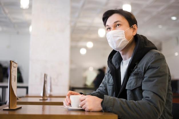Seitenansicht des mannes mit der medizinischen maske, die an einem tisch sitzt, um kaffee zu haben Kostenlose Fotos
