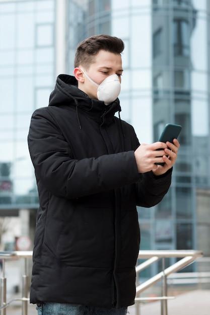 Seitenansicht des mannes mit der medizinischen maske, die sein telefon in der stadt betrachtet Kostenlose Fotos