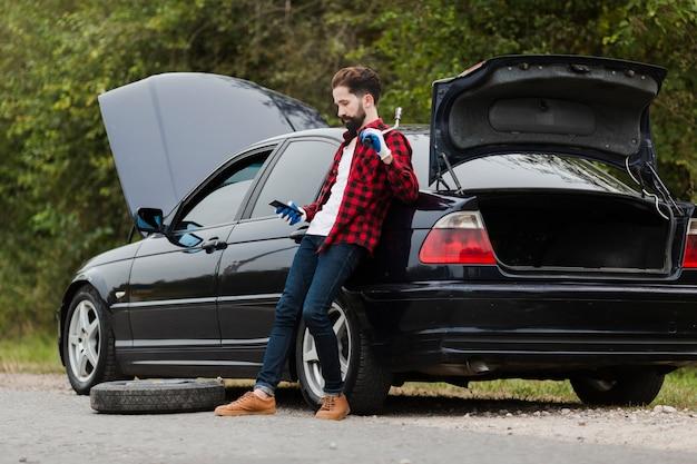 Seitenansicht des mannes mit telefon und schlüssel Kostenlose Fotos