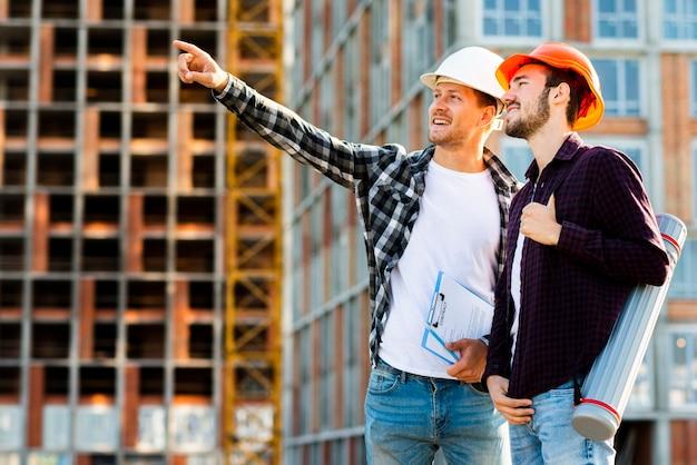 Seitenansicht des mittleren schusses des ingenieurs und des architekten, die bau überwachen Kostenlose Fotos