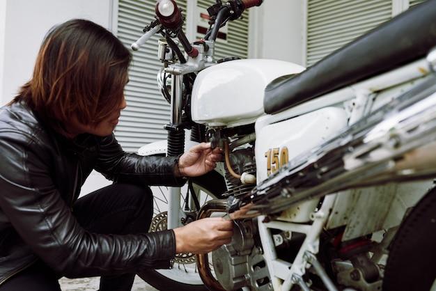 Seitenansicht des motorradfahrers sein fahrrad vor einer fahrt überprüfend Kostenlose Fotos