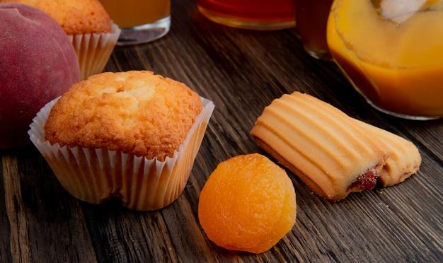 Seitenansicht des muffins mit getrockneten aprikosen und keksen auf rustikalem holz Kostenlose Fotos