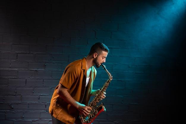 Seitenansicht des musikers, der das saxophon im scheinwerferlicht spielt Kostenlose Fotos