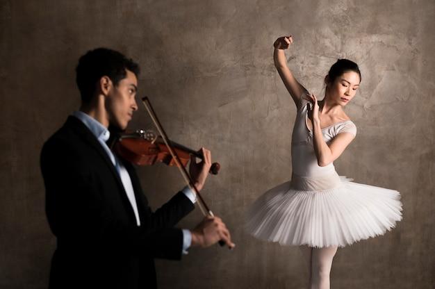 Seitenansicht des musikers, der geige und ballerina tanzt Kostenlose Fotos